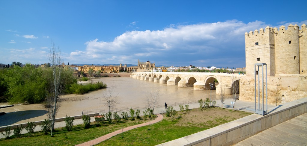 A view of Cordoba, with the ancient Roman bridge in the foreground, while a dark weather front approaches.